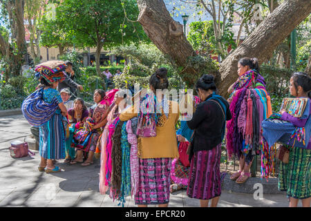 Women in traditional Maya dress with cloth to sell in Central Park in Antigua Guatemala - Stock Photo