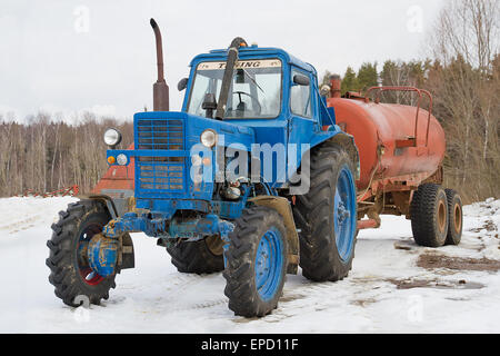 Old farm tractor with trailer in winter - Stock Photo