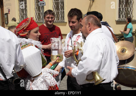 Young woman at the ride of Kings in Prague, dressed in typical Moravian costume is serving new wine to the musicians - Stock Photo
