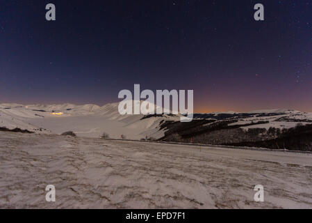 Piano Grande of Castelluccio di Norcia in winter with snow by night, Sibillini mountains NP, Umbria, Italy - Stock Photo