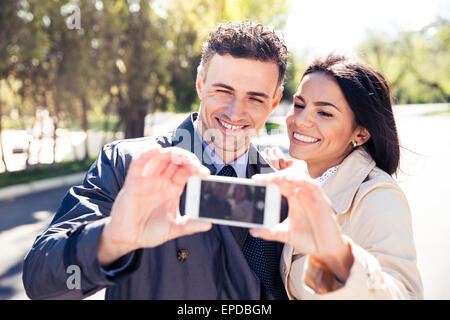 Smiling couple making selfie photo on smartphone in park - Stock Photo