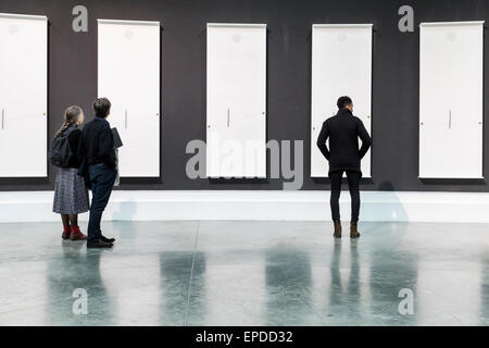 Couple and Trendy young man dressed in black admires black and white artwork at 'Palais de Tokyo' modern art gallery, - Stock Photo