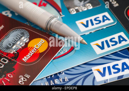 Tambov, Russian Federation - March 31, 2015 Visa and Mastercard credit cards with  ballpoint pen on black background. - Stock Photo