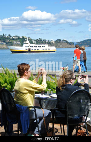 tourists take photos on i phones at Sausalito Cafe - Stock Photo
