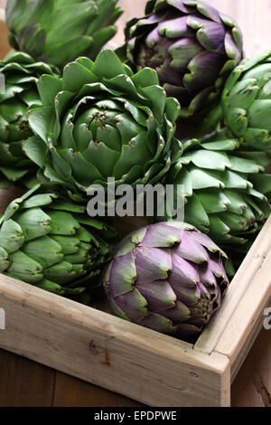 artichokes in wooden box isolated on wooden background - Stock Photo