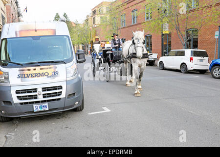 Tourists take an evening carriage ride in downtown Bend, Oregon, during the spring. - Stock Photo