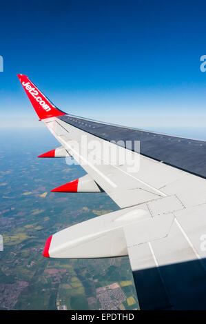 Looking out along the wing of a Jet2.Com Boeing 737 aeroplane during flight over the English countryside - Stock Photo