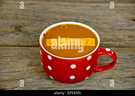 Tomato soup in a red soup mug with white polka dots on rustic wood ...