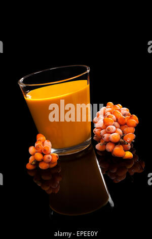 Sea buckthorn juice and berries isolated on black background. Alternative medicine. Healthy fruit eating. - Stock Photo