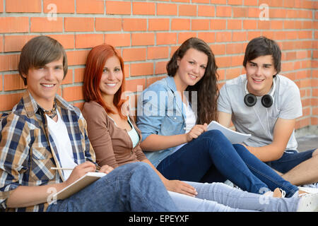 Group of friends students sitting in row - Stock Photo