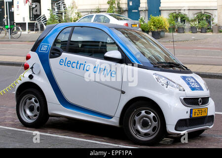 Electric car charging from an on-street Electric charge station - Stock Photo