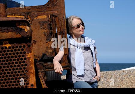 senior woman leaning on rusty tractor on beach - Stock Photo
