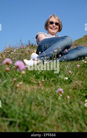 senior woman laying on grass - Stock Photo
