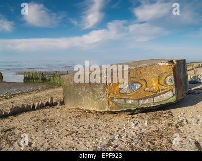 German ww2 d-day concrete beach defences painted with a graffiti face on Gold Beach, Asnelles, Normandy France - Stock Photo