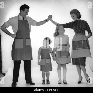 Family modelling a set of aprons for Reveille. 2nd December 1957 - Stock Photo