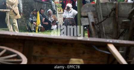 Radebeul, Germany. 16th May, 2015. A woman dressed in 19th century clothing takes a picture of an reenactment of - Stock Photo