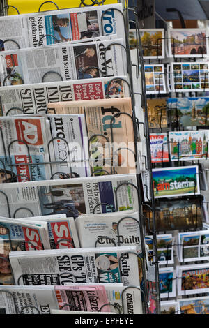 International Newspapers and post cards on a stand - Stock Photo