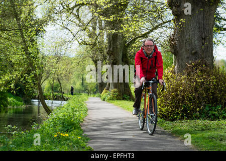 a middle aged man cycling cyclist on his bike on the path by the river Churn, on a spring  afternoon , Cirencester, - Stock Photo