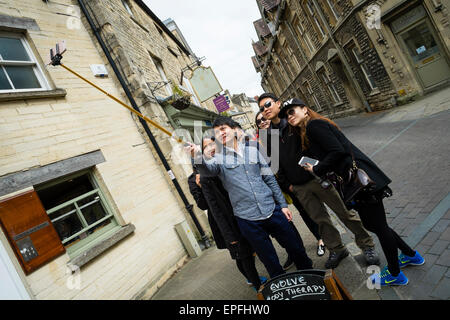 A group of young happy smiling Chinese tourists taking a selfie on a stick in the centre of Cirencester, Gloucestershire, - Stock Photo