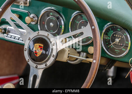 An image of A Porsche 356 steering wheel with green leather dashboard trim - Stock Photo
