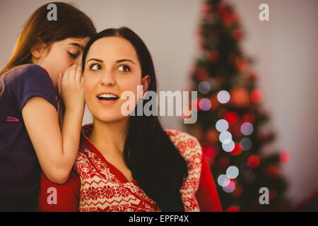 Daughter telling her mother a christmas secret Stock Photo ...