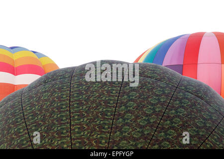Tops of three colorful  hot air balloons against a washed out morning sky. - Stock Photo