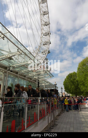 A queue of tourists waiting at the London Eye sponsored by Coca Cola - Stock Photo