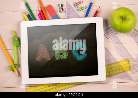 Composite image of digital tablet on students desk - Stock Photo