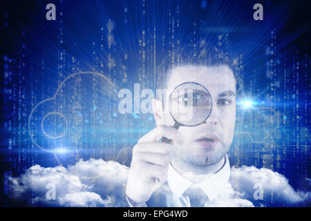 Composite image of businessman looking through magnifying glass - Stock Photo