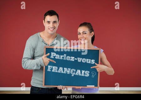 Composite image of smiling young couple pointing at sign they are holding - Stock Photo
