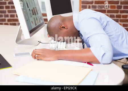 Businessman resting head on computer keyboard in office - Stock Photo