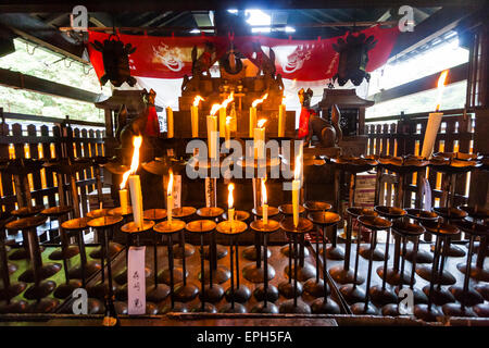 Japan, Kyoto, Fushimi Inari shrine Small sub shrine, very dark inside with candles burning left as offerings - Stock Photo