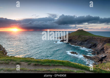 A dramatic sunset as storm clouds gather over The Rumps, a coastal promontory jutting out in to the Atlantic ocean - Stock Photo