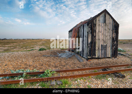 An abandoned fishing shack on a shingle beach in Kent - Stock Photo