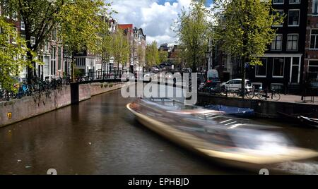 Boat in motion navigates the Brouwersgracht canal Amsterdam - Stock Photo