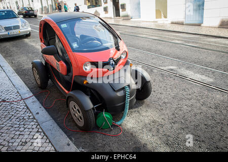 Renault ZE Twizy electric car parked in the street plugged in and charging - Stock Photo