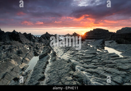 Dramatic sunset on the rocky beach at Hartland Quay on the north coast of Devon near Bideford - Stock Photo
