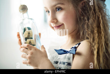 Little kid holding a bottle with a ship - Stock Photo