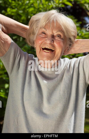 Senior lady with a good sense of humour having a hearty laugh as she enjoys the sunshine outdoors in her garden - Stock Photo