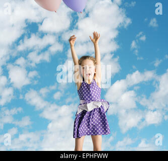 Cute little girl flying up to the sky - Stock Photo