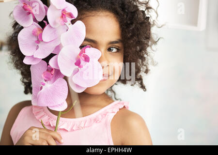 Little joyful girl holding a beautiful flower - Stock Photo