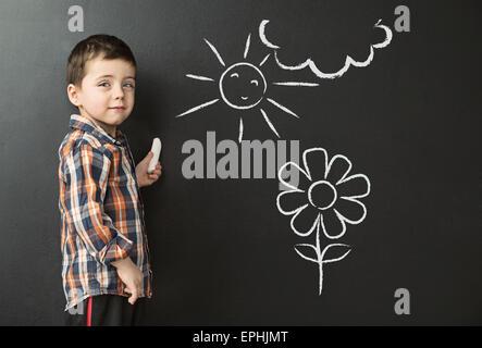 Little boy drawing on the blackboard - Stock Photo