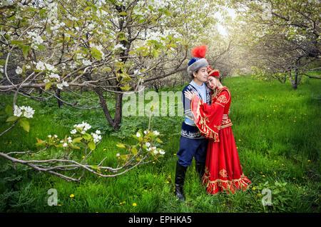 Couple in Kazakh costume in Spring Blooming apple garden of Almaty, Kazakhstan, Central Asia - Stock Photo