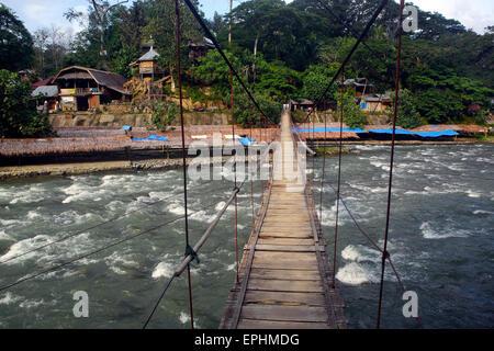 Wooden suspension bridge across the Bohorok River in Bukit Lawang, Sumatra - Stock Photo