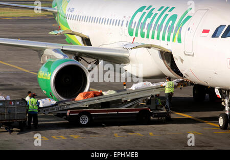 Loading a Citilink airline on the tarmac in Bali, Indonesia - Stock Photo