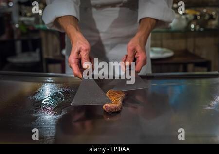 Chef cooking wagyu beef in Japanese teppanyaki restaurant, Tokyo, very shallow focus - Stock Photo