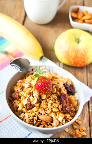 Healthy breakfast with wholegrain muesli, fruits, nuts and milk over rustic wooden table - Stock Photo