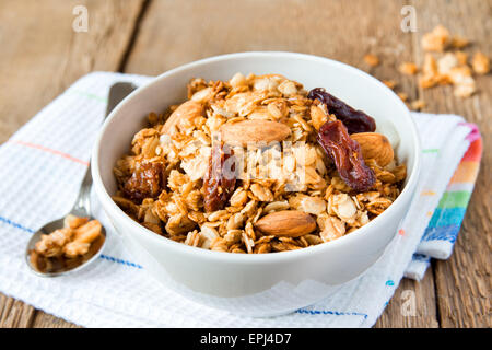 wholegrain muesli for breakfast, with lots of dry fruits, nuts and grains close up, horizontal, on wooden table - Stock Photo