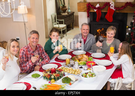 Smiling family toasting to camera during christmas dinner - Stock Photo