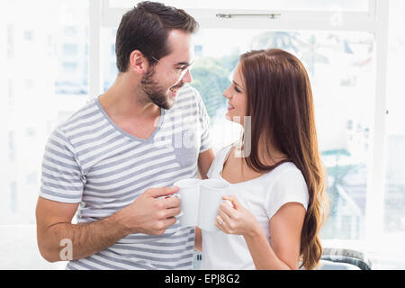 Young couple toasting their coffees - Stock Photo